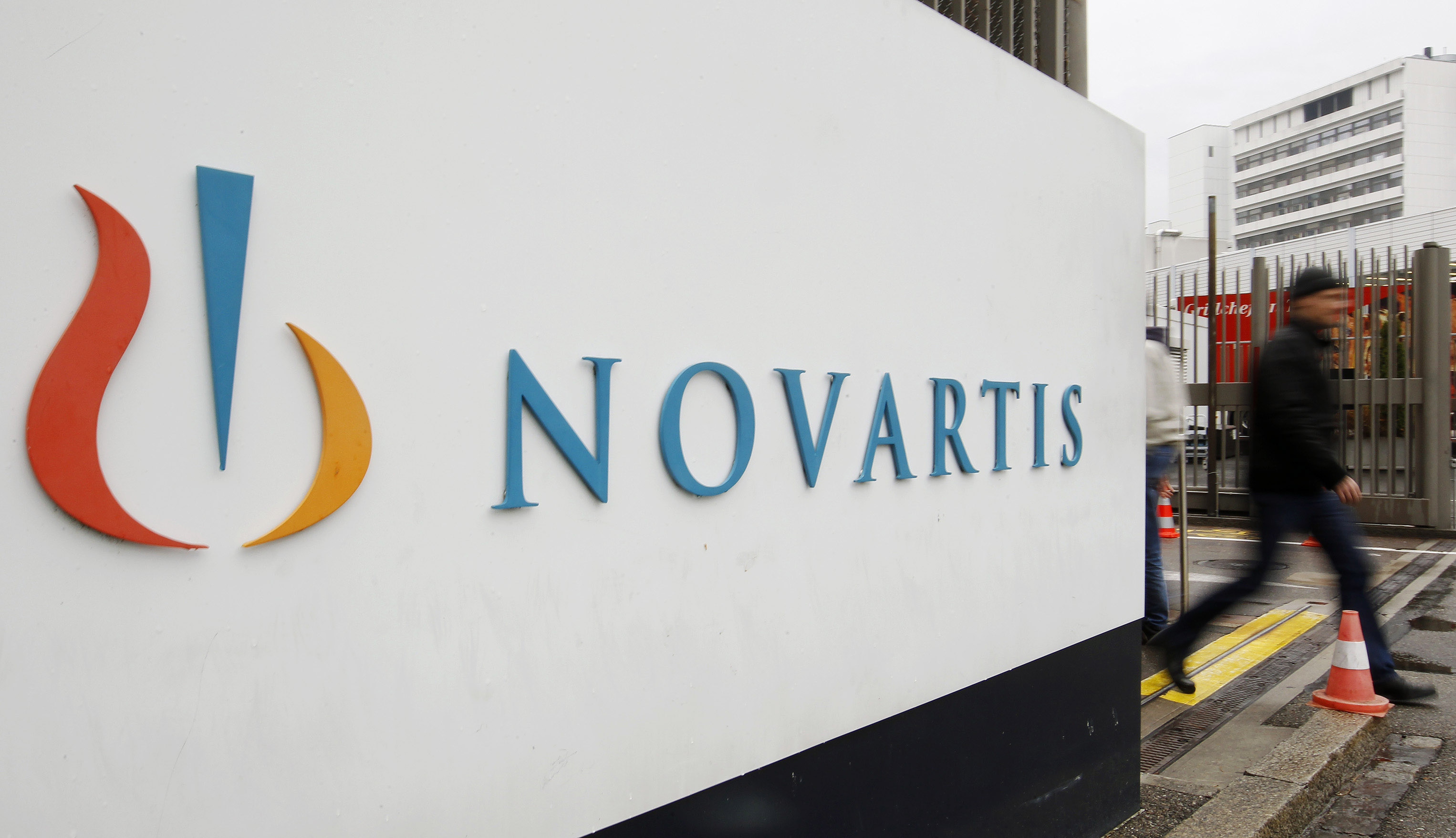 File photo of a man walking past the logo of Swiss drugmaker Novartis AG in front of a plant in Basel