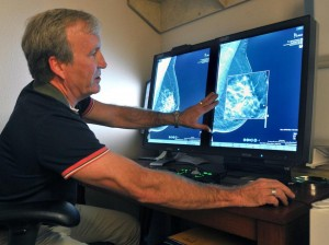 A radiologist compares a 2D and a 3D image of the female breast.