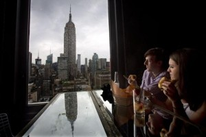 People sit and eat hot dogs and look at the Empire State Building after a hot dog eating competition was moved indoors due to bad weather on Independence Day in the Manhattan borough of New York