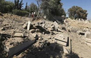 Palestinians look for the graves of their relatives at a cemetery which witnesses said was hit by an Israeli air strike in Gaza City