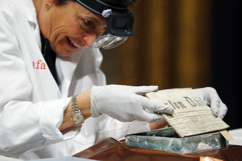 Conservator Pam Hatchfield removes a newspaper from a time capsule, which was placed under a cornerstone of the State House in 1795, at the Museum of Fine Arts, Boston