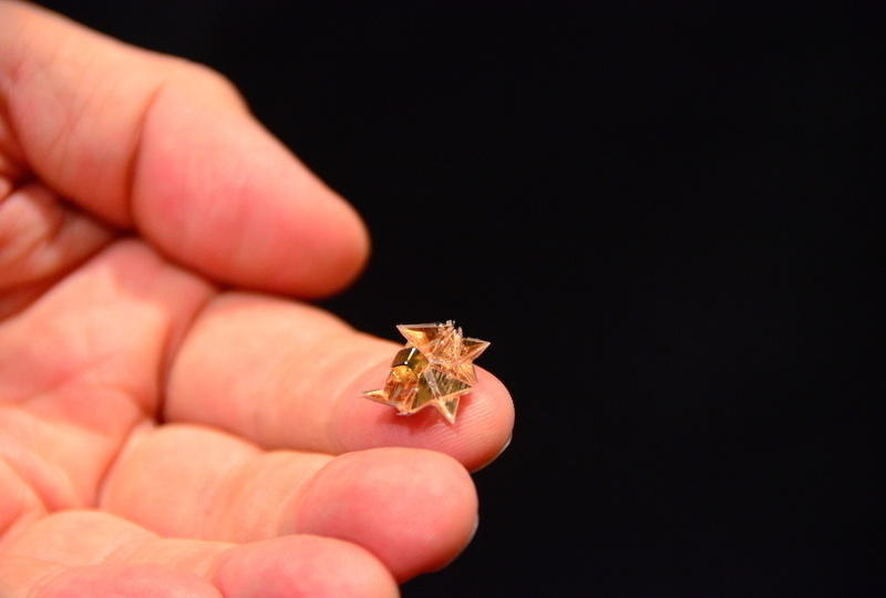 """alt=""""scientist holding the origami robot in his hand"""""""