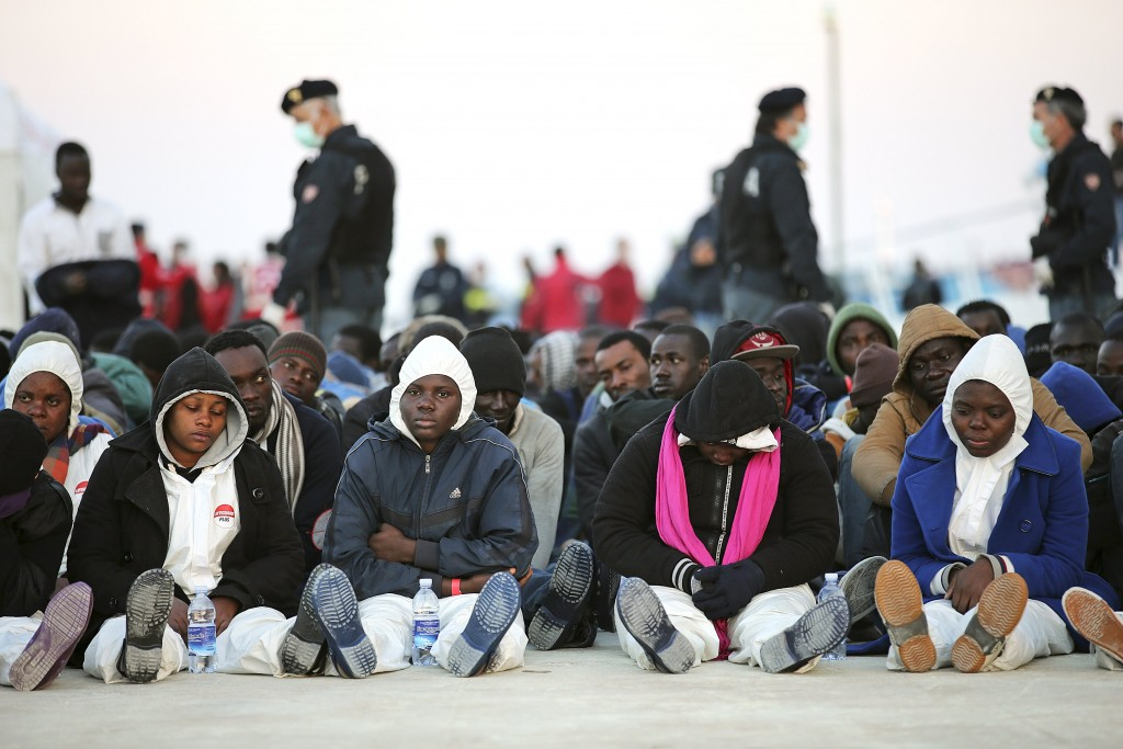 """""""Migrants rest after they disembarked in the Sicilian harbour of Augusta, April 16, 2015"""""""