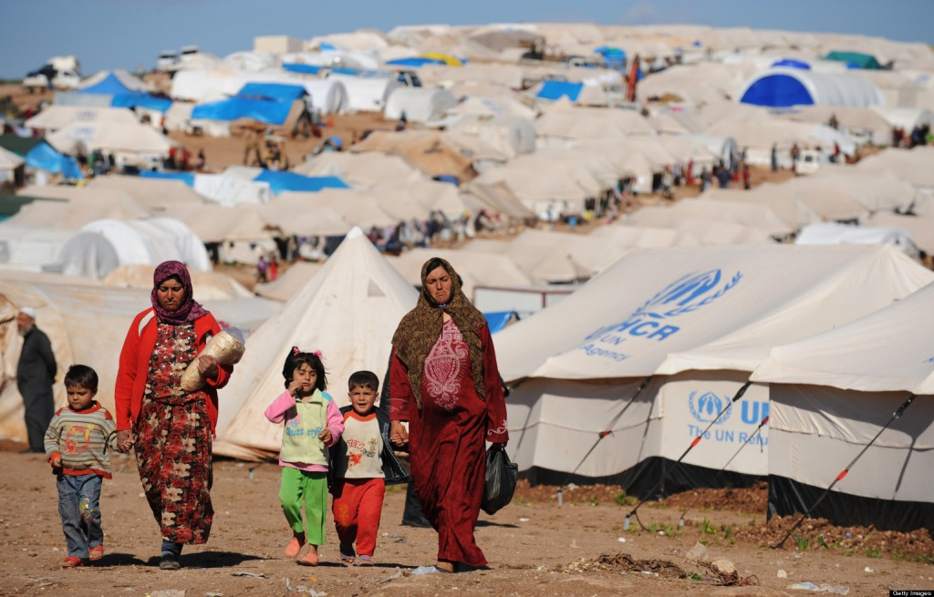 """alt=""""Syrian internally displaced people walk in the Atme camp, along the Turkish border in the northwestern Syrian province of Idlib, on March 19, 2013. The conflict in Syria between rebel forces and pro-government troops has killed at least 70,000 people, and forced more than one million Syrians to seek refuge abroad"""""""