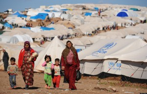 "alt=""Syrian internally displaced people walk in the Atme camp, along the Turkish border in the northwestern Syrian province of Idlib, on March 19, 2013. The conflict in Syria between rebel forces and pro-government troops has killed at least 70,000 people, and forced more than one million Syrians to seek refuge abroad"""