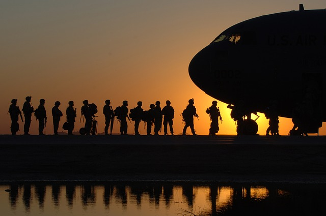 """""""military male and female soldiers getting on a plane"""""""