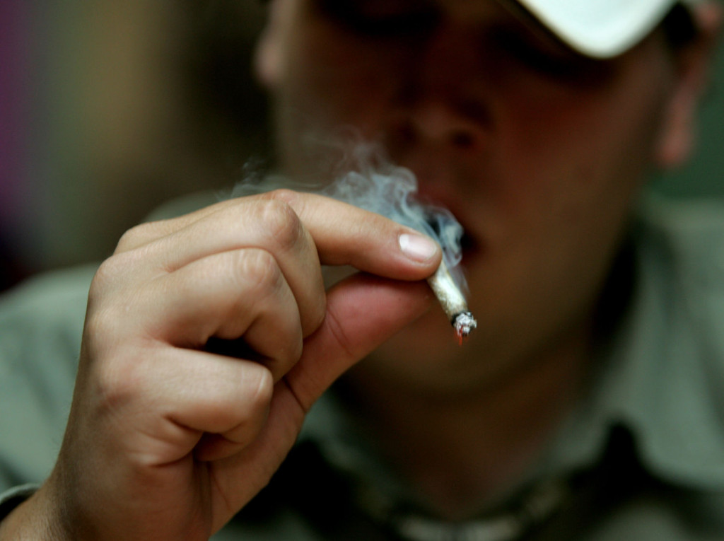"""alt=""""A patient puffs on medicinal marijuana in the San Francisco Patients Cooperative on June 7, 2005 in San Francisco. The Supreme Court dealt a blow to the medical marijuana movement 6/6, ruling that the federal government can still ban possession of the drug in states.   (UPI Photo/Terry Schmitt)"""""""
