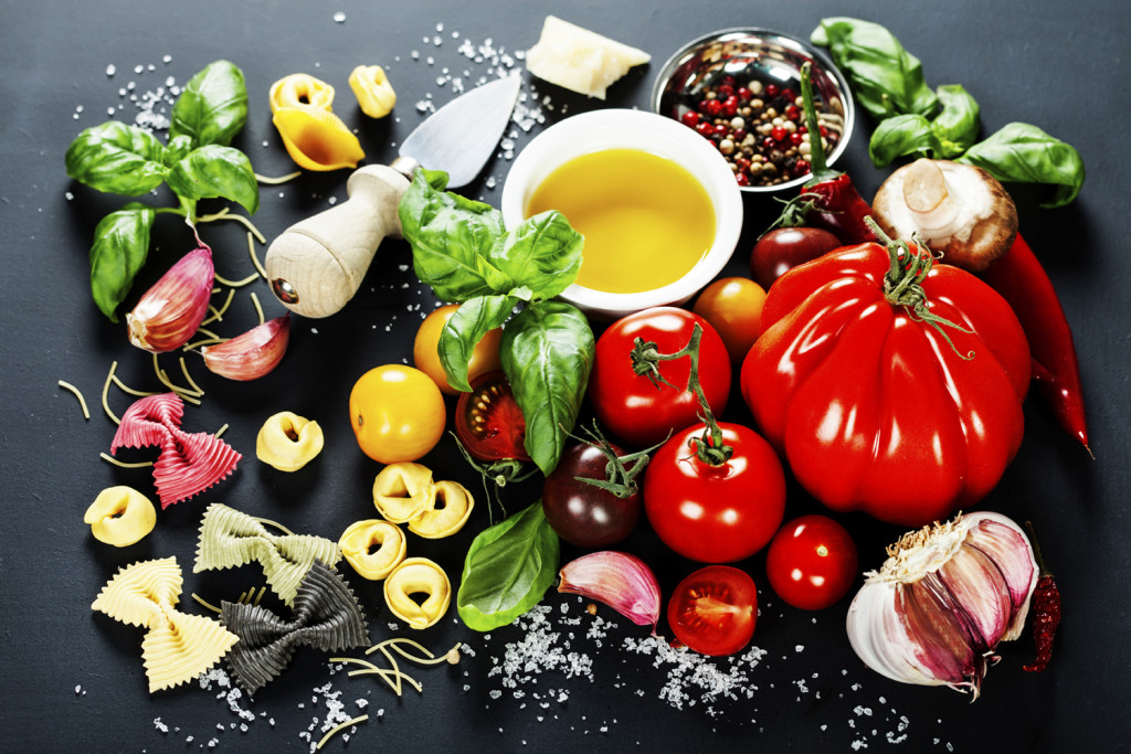 "alt=""Italian ingredients - pasta, vegetables, spices, cheese - on dark background"""