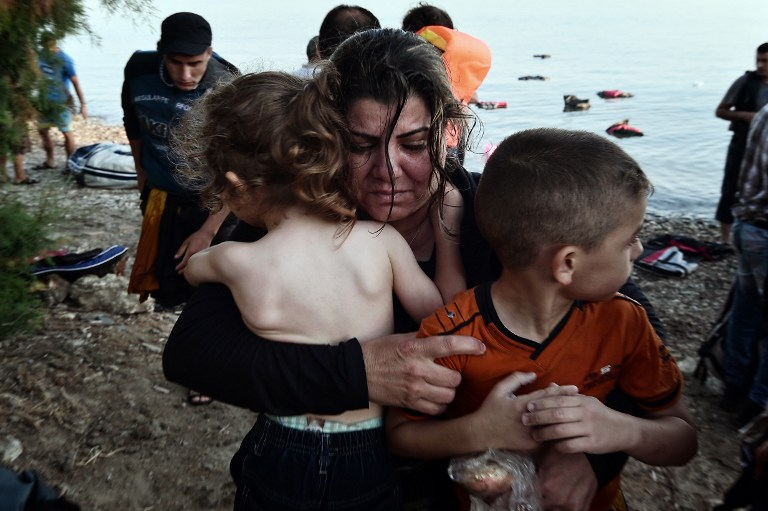"alt=""A Syrian migrant holds her children as they arrive on an overcrowded dinghy on a beach near the port on the Greek island of Kos on August 15, 2015. A ferry boat has been sent by the Greek government to the resort of Kos to speed up the registration process of hundreds of Syrian refugees, docked on August 14 afternoon at the harbour. The Eleftherios Venizelos will stay moored in Kos for some two weeks, during which time authorities will register newcomers to the island, which is already overflowing with refugees and migrants. AFP PHOTO /LOUISA GOULIAMAKI"""