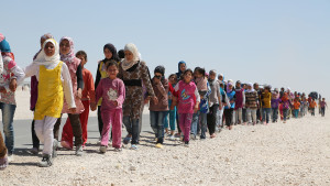 """alt="""" Syrian children march in the refugee camp in Jordan. The number of Children in this camp exceeds 60% of the total number of refugees hence the name """"Children's camp"""". Some of them lost their relatives, but others lost their parents."""""""