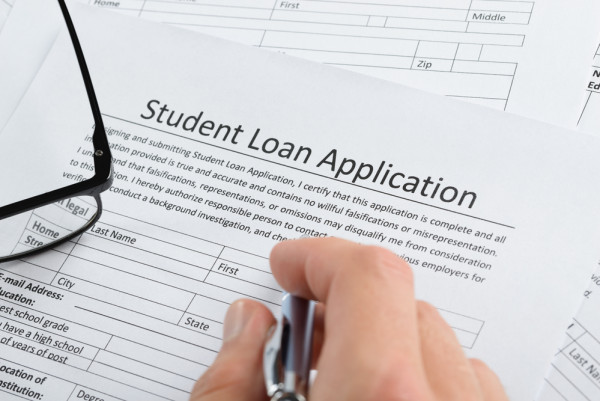 closeup of a hand with pen over a student loan application
