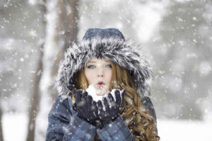 Young girl playing with snow outdoors