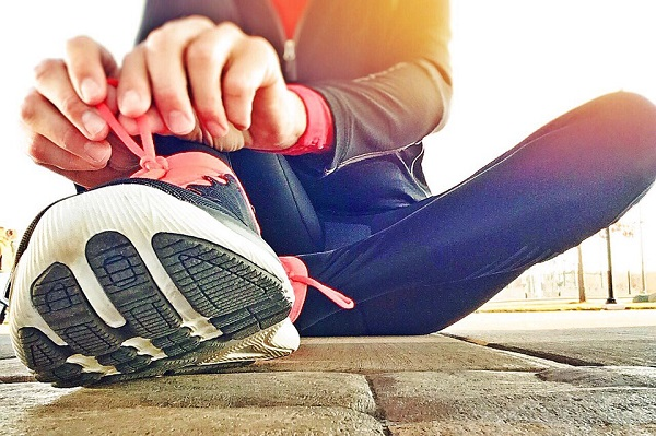 woman tying running shoes for stroke prevention