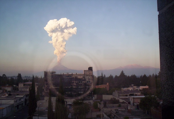 erupting volcano in the distance