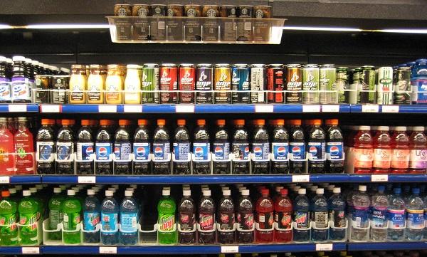several shelfs with soda drinks