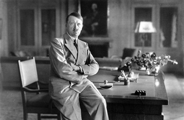 Adolf Hitler sitting on desk facing camera