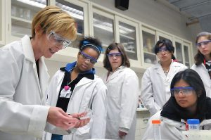Female chief scientist showing an experiment to her students
