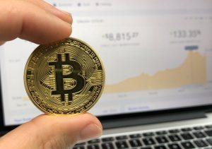 Man holding round Bitcoin in hand