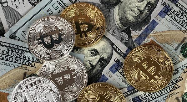 Bitcoin coins on 100-dollar bills