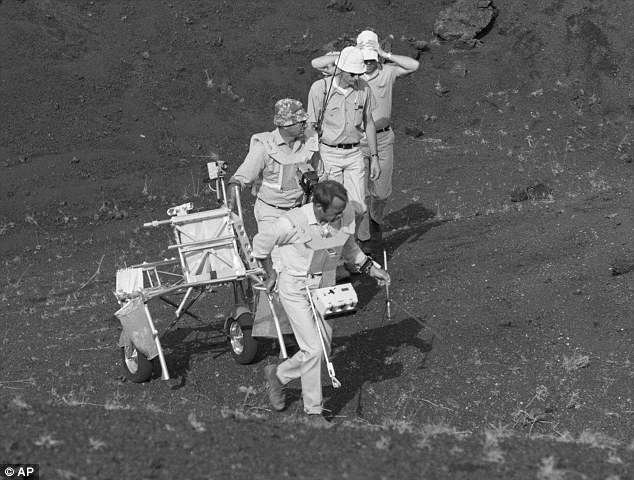 1970 image: Apollo 14 astronauts Alan Shepard, Edgar Mitchell and Stuart Roost training with a Modular Equipment Transporter along with another unidentified individual.