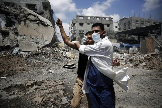 A medic helps a Palestinian in the Shejaia neighbourhood, which was heavily shelled by Israel during fighting, in Gaza City