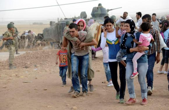 Syrian Kurds walk after crossing into Turkey at the Turkish-Syrian border, near the southeastern town of Suruc in Sanliurfa province