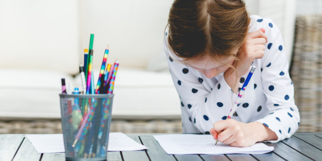 "alt=""Young girl writing out her homework"""