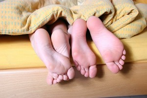 feet of couple poking out of the blanket