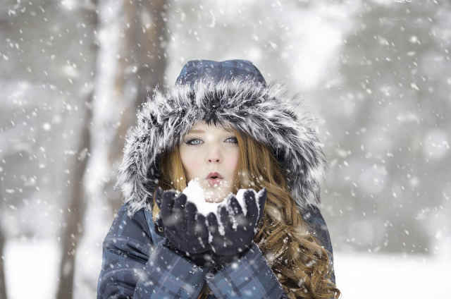 Young woman playing with snow outdoors