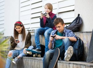 Teenagers looking at their smartphones
