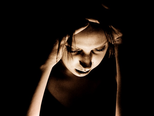 woman with migraine clutching her temples
