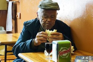Old man eating a sandwich