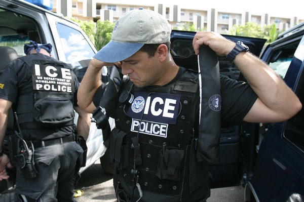 ICE SWAT officer putting on a vest
