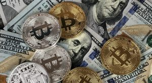 Bitcoin coins on 100-dollar bills