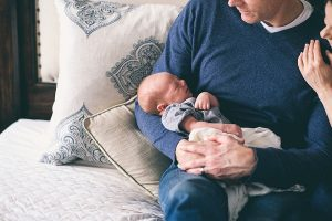 Father holding newborn child in his arms