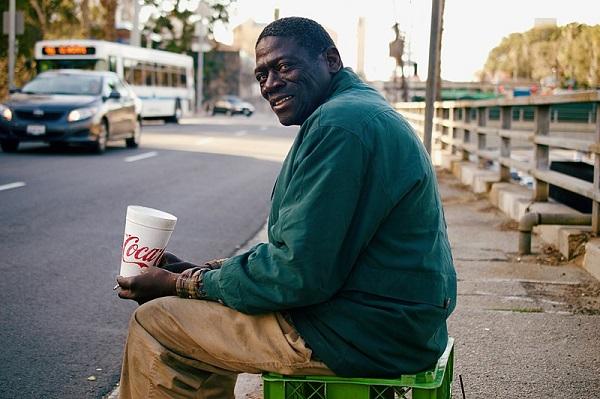 Black homeless man begging