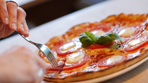 Slicing an Italian pizza